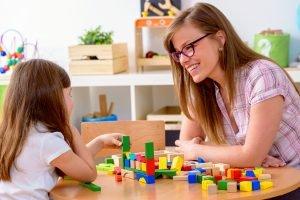 Preschool Teacher and Cute Girl Having Fun Time Playing