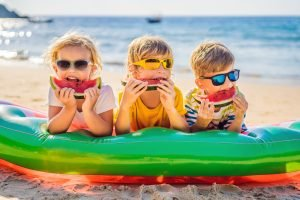 Children eat watermelon on the beach in sunglasses.